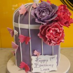 double-height-tier-round-birthday-cake-purple-bird-cage-flowers