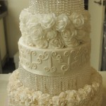 four-tier-round-wedding-cake-white-flowers-lights-crystals-icing-details