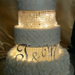 three-tier-round-wedding-cake-white-lights-crystals-lace-flowers